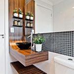 Banheiro com bancada curva em madeira, painel e prateleiras na lateral.